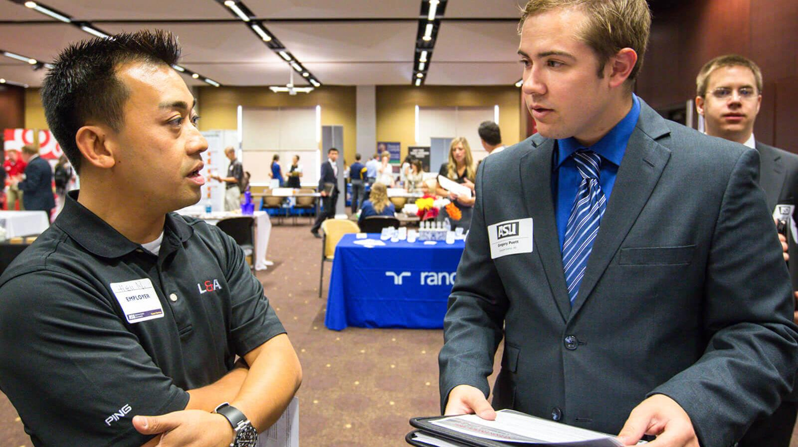A student speaks to a recruiter at a career fair