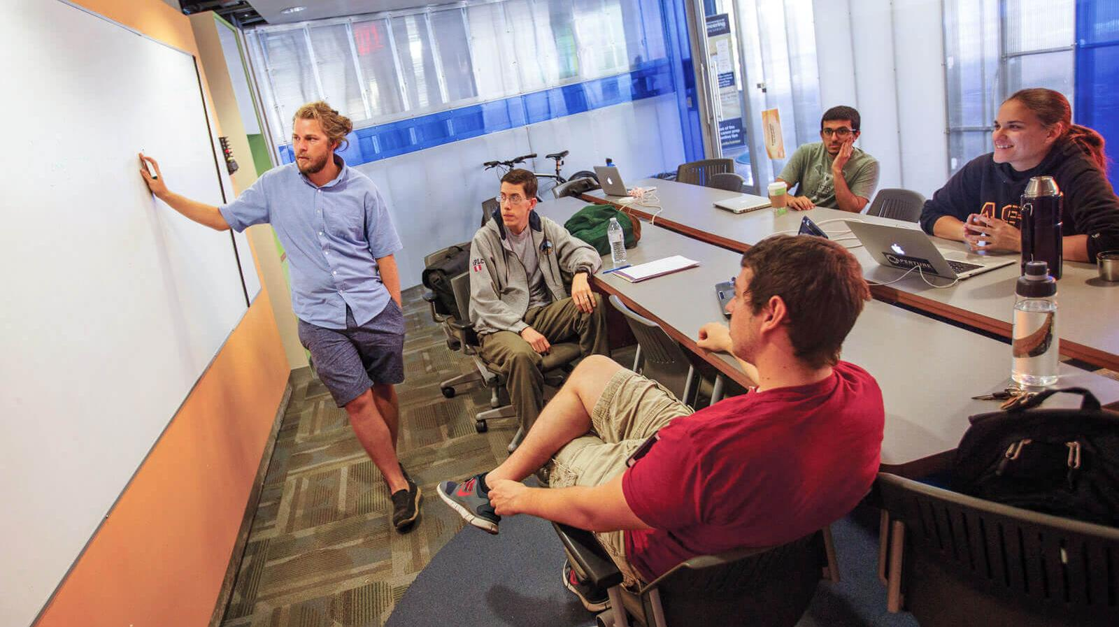 Students in a startup discuss ideas around a whiteboard